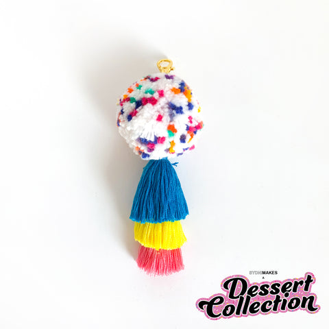 A white pom pom keychain dotted with pink, blue, yellow, green, and purple above a 3-tier tassel in blue, yellow and pink, with gold hardware, on a white background.