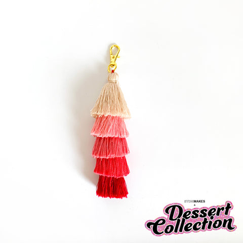 A tassel keychain made of a 5-tier tassel in shades of cream, pink, and red with gold hardware sits on a white background.