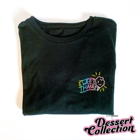 "A folded black tee shirt has the words ""Sweet Thang"" and cotton candy embroidered with multicolored thread."