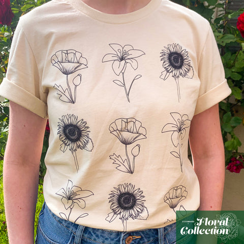 A woman's torso displaying a cream colored t-shirt with three rows of simple black line art florals printed onto it.