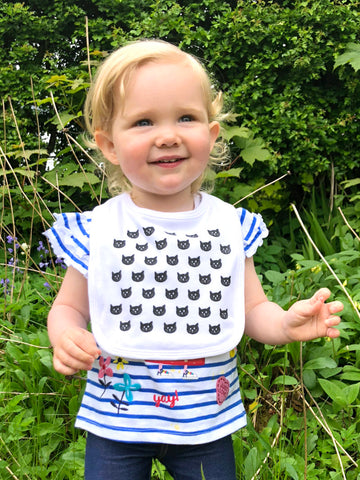 Image of little girl wearing a white bib with a modern black cat pattern