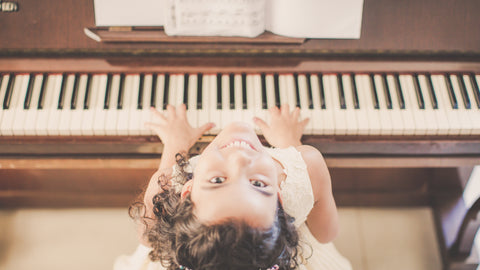 Girl looking up sitting at a piano