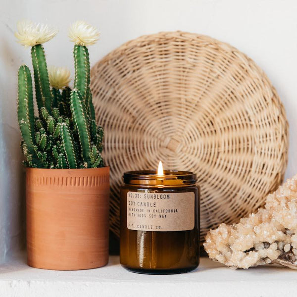 Burning Sunbloom PF Candle Co classic line candle on a shelf next to a cactus, gemstone, and a wicker basket