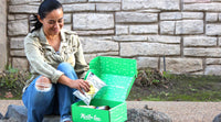 woman in a park holding potato chips in a green snack subscription box munchie case