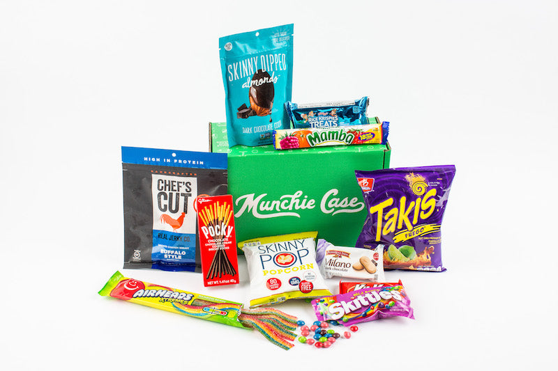 Variety of snacks stacked around snack subscription box munchie case