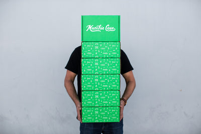 Customer holding stacked snack subscription box delivery