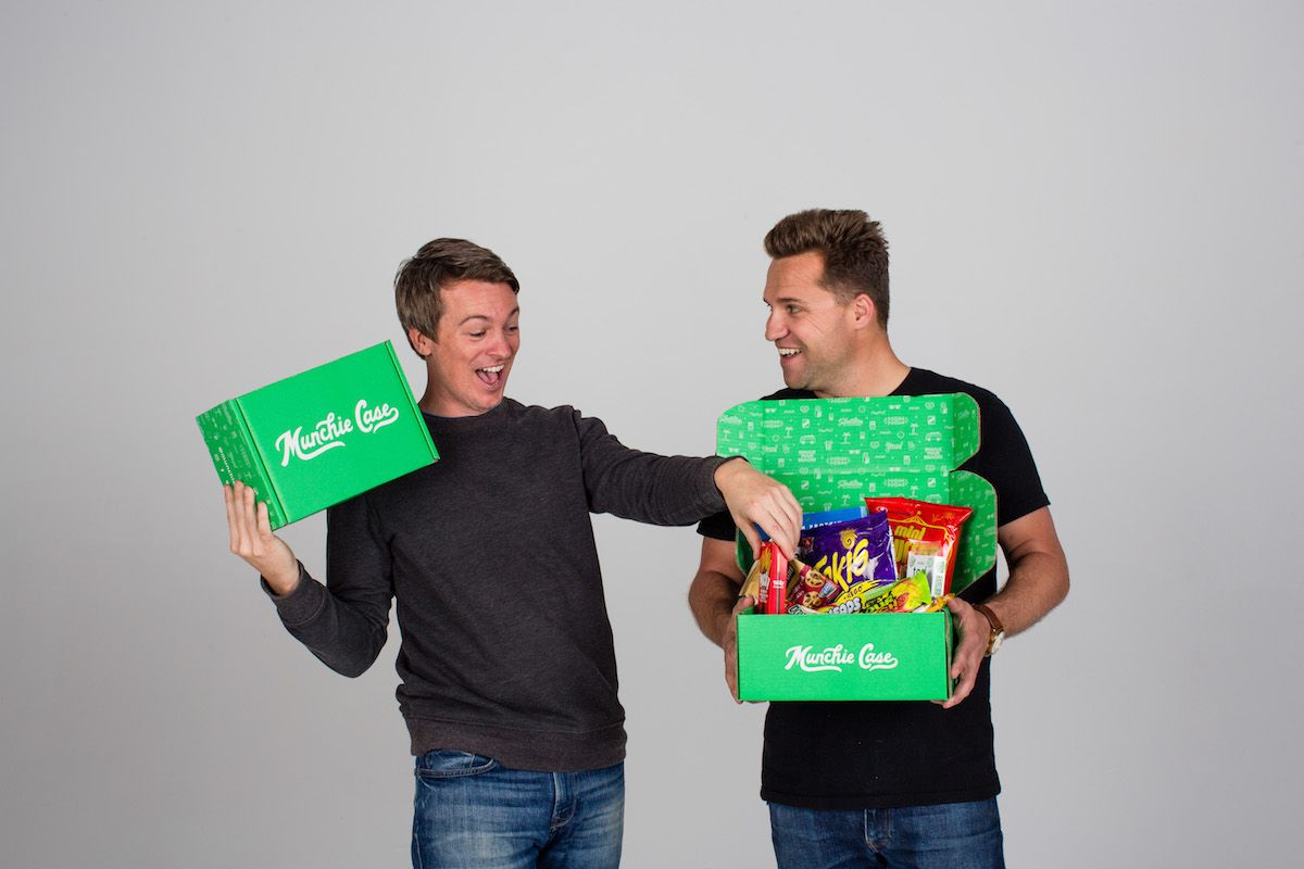 Founders of subscription box munchie case holding snack boxes and having fun