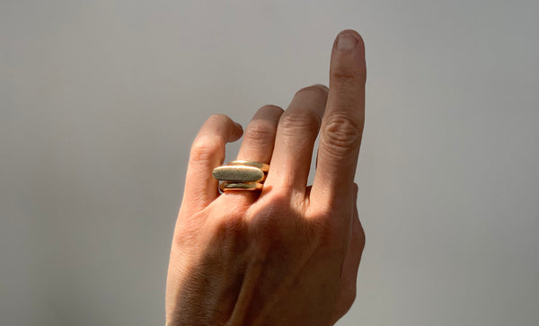 Closeup of hand against a white background wearing PIEDRA and DEDO stacking rings in the sunlight