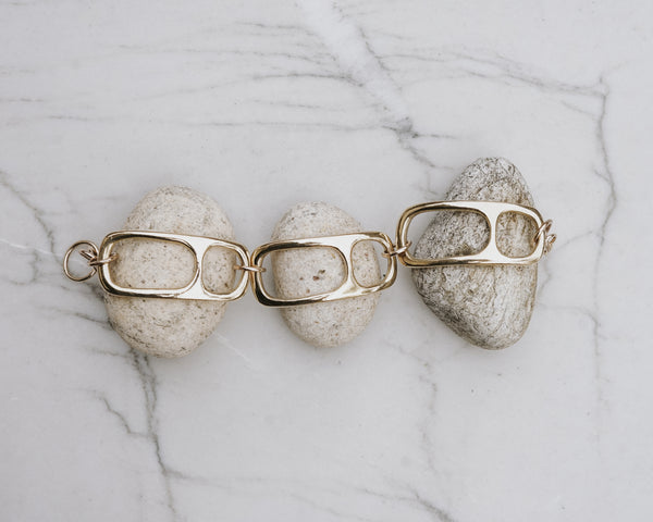 MOURA link bracelet in polished bronze displayed on rocks