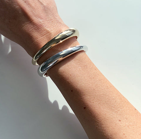Bronze and sterling silver highly polished CALA cuffs on a wrist