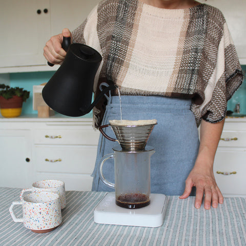 woman making pourover coffee wearing a blue apron in a blue and white kitchen