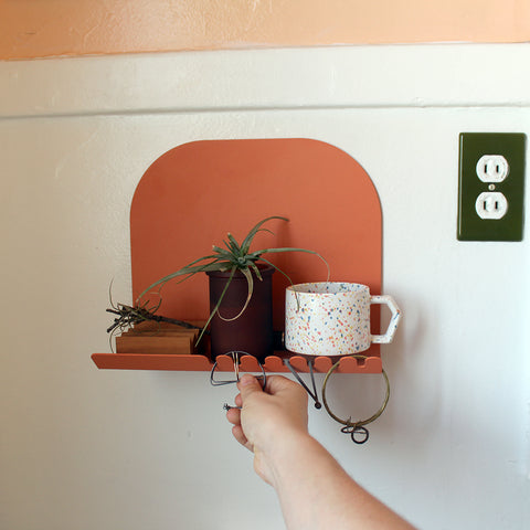 Terracotta colored bathroom shelf with candle, airplant, mug and earrings