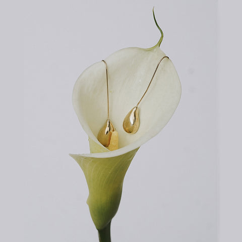 bronze teardrop earrings suspended inside a cala lily flower