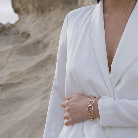 woman in white jacket and bronze MOURA link bracelet standing with arm across her waist in front of sand dunes.