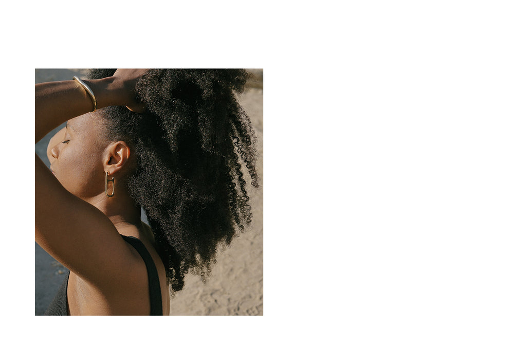 MOURA bronze sculptural rectangular hoop earrings on model with natural hair style on the beach