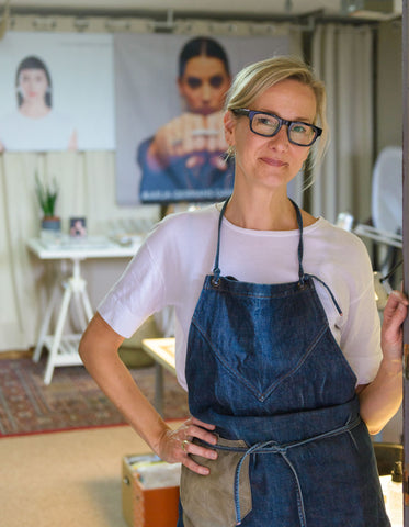 Jeweler in glasses and an apron standing at the entrance of her studio