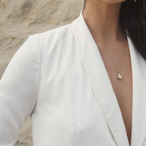 TIRSO polished bronze droplet necklace from MGG Studio shows on model in white blazer on the beach.