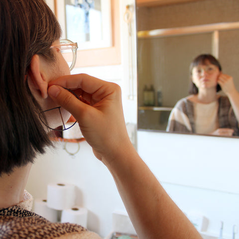 woman looking in a mirror and putting on a pair of oxidized silver and gold hoop earrings