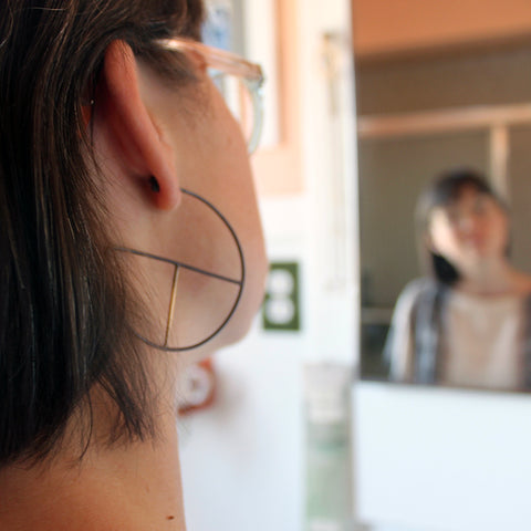 Woman looking in the bathroom mirror wearing a pair of black and gold geometric hoop earrings
