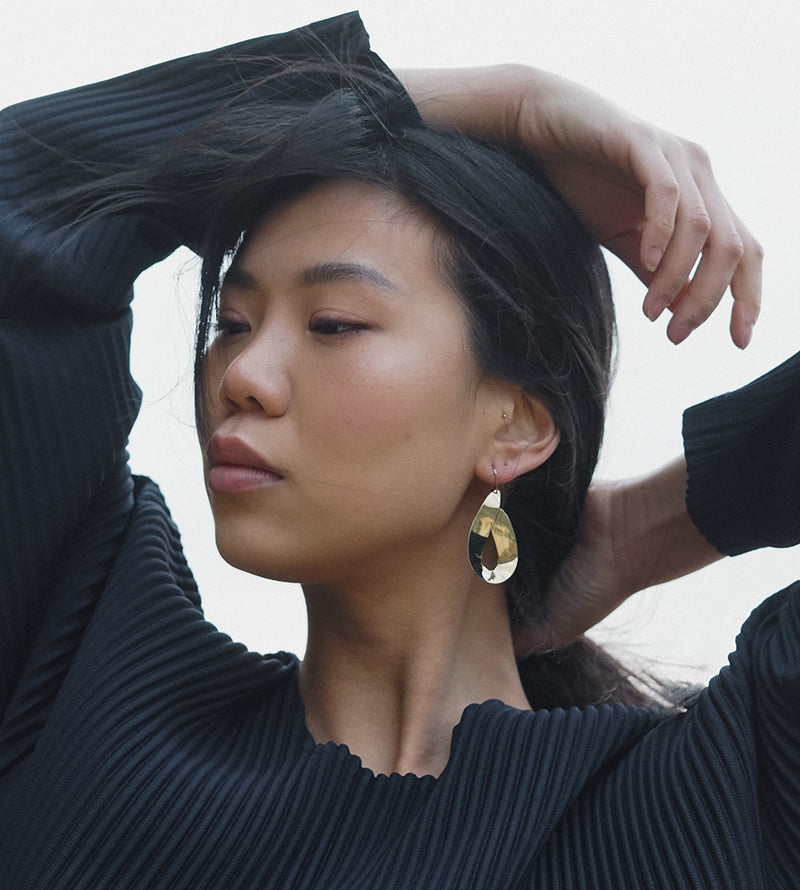 BELO statement earring in high polish brass from MGG Studio on model on cloudy day