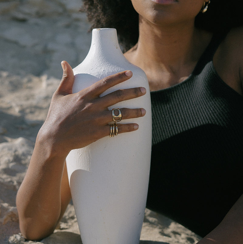 LAGOS polished bronze sculptural statement ring with unique openings on model holding vase