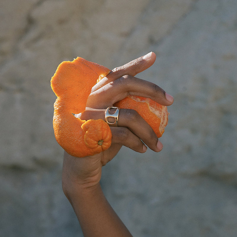 unique LAGOS statement ring in polished bronze from MGG Studio on model holding orange