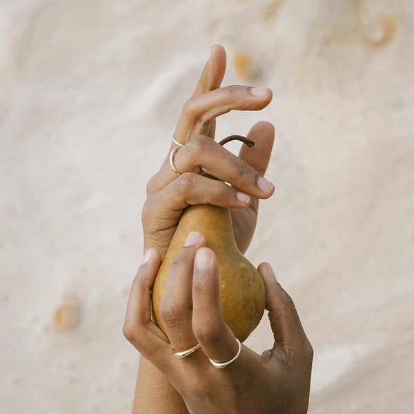 TAVIRA slim and sculptural stacking rings from MGG Studio on model's hands