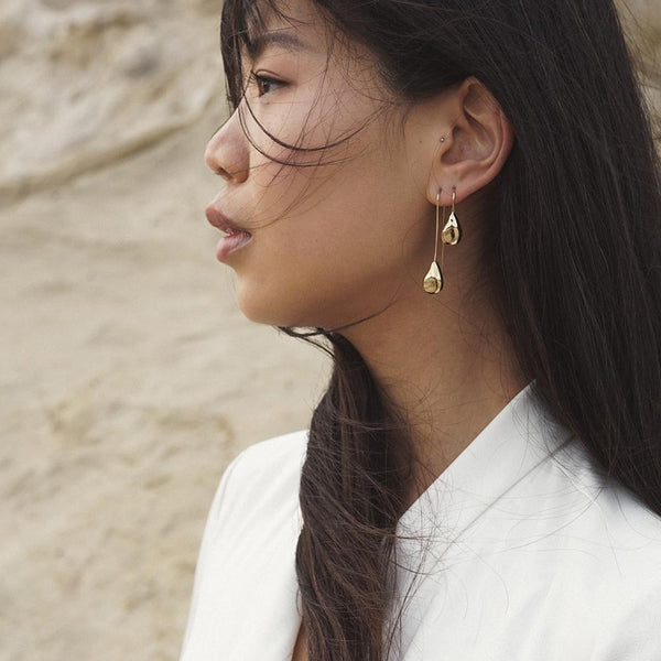 TIRSO long and short drop earrings in polished bronze from MGG Studio on model