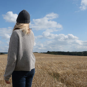 female model in field | wears Norway beanie hat in merino wool grey | The Knit Kit Company
