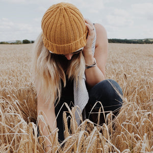 female model in field | wears norway beanie hat in merino wool yellow | The Knit Kit Company