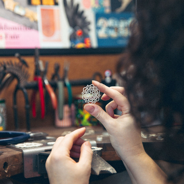 Inspecting mandala pendant silver at jewellers workbench