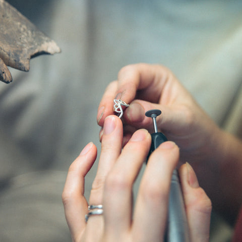 two hands holding silver v shape ring and flexishaft to polish ring