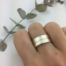 Wide silver ring with gold stripe.