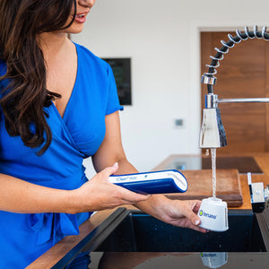 Image of lady filling iclean mini base with water from the tap