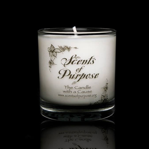 A white candle in a clear glass candle holder by Scents of Purpose on a black background.