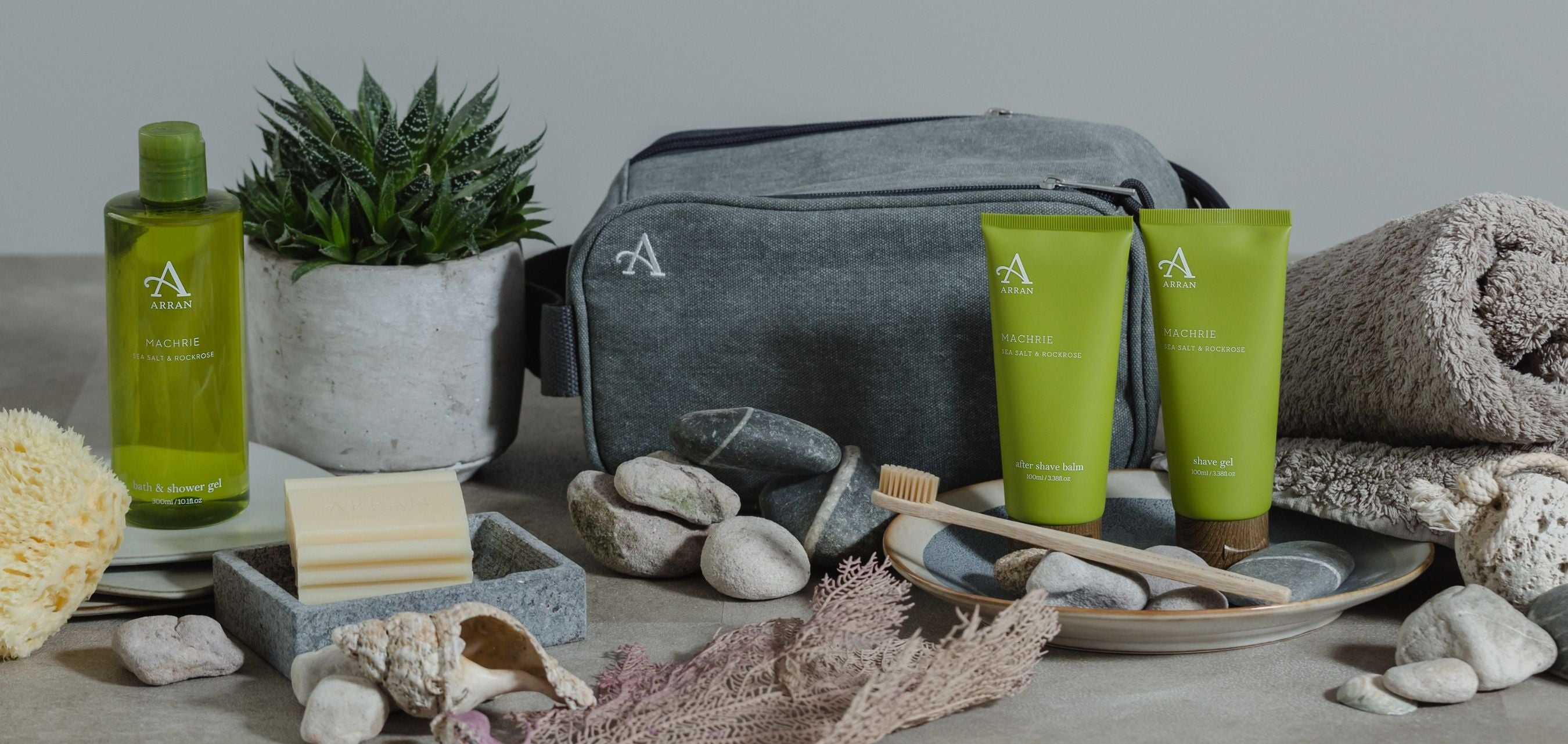Grey canvas bag with green shower gel bottle, shave gel and after shave balm, surrounded by grey pebbles and green house plant.