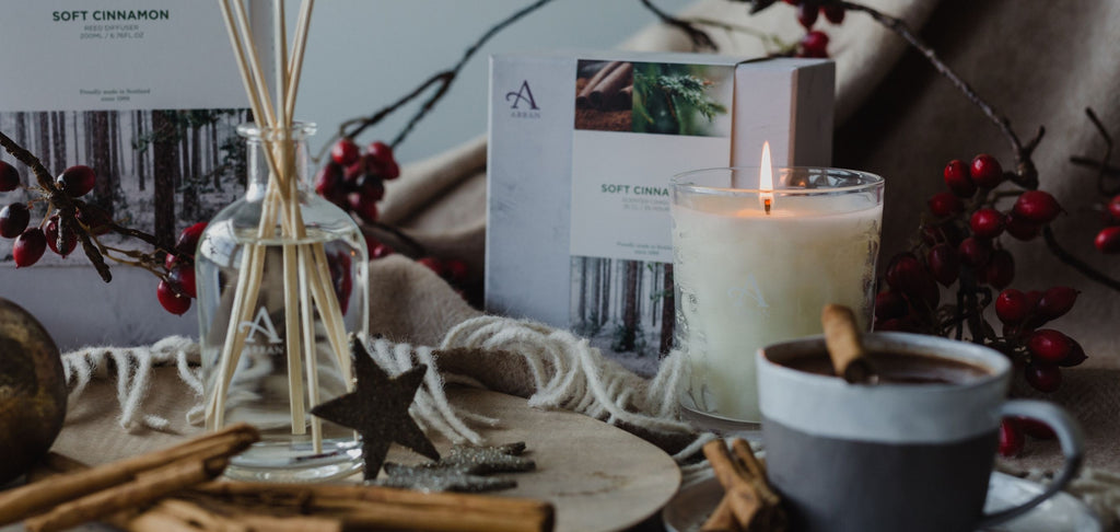 Lit scented candle and reed diffuser placed beside cinnamon sticks, mug and blanket.