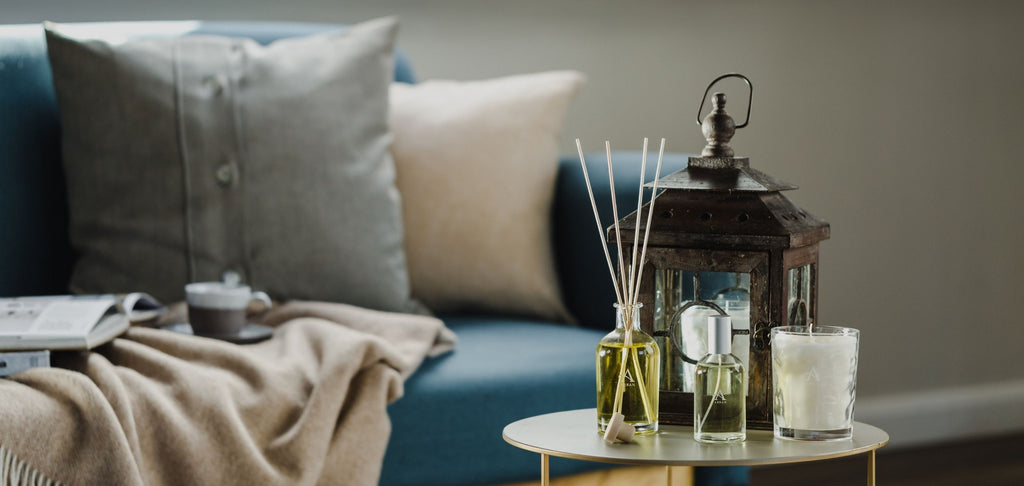 Candle, Diffuser and Room Spray on small table in living room with navy couch, neutral blanket and cushions in background.