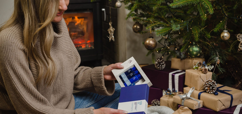 Woman opening Christmas gift by fireplace with Christmas tree in background.