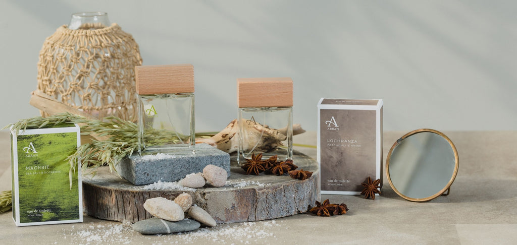 Two men's eau de toilette bottles, standing upright beside gift boxes and travel-sized mirror.