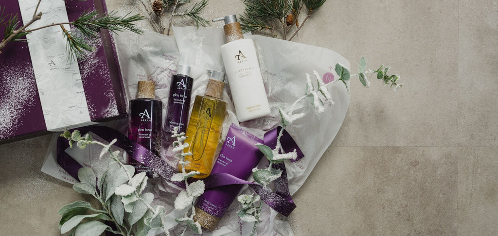 ARRAN purple gift box with hand wash, hand cream, shower gel and body lotion, surrounded by frosted eucalyptus and white tissue paper