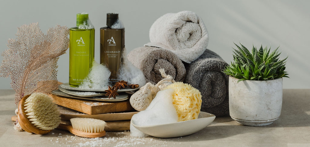 Machrie and Lochranza Men's Shower Gels sitting upright with sponge, body brush, grey towels and house plant.