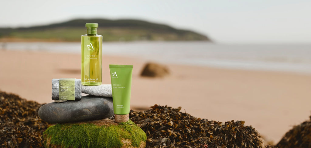 Image of men's shower gel and soap on a beach on the Isle of Arran