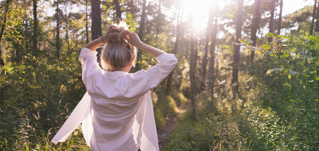 Image of woman walking in a forest with sunshine