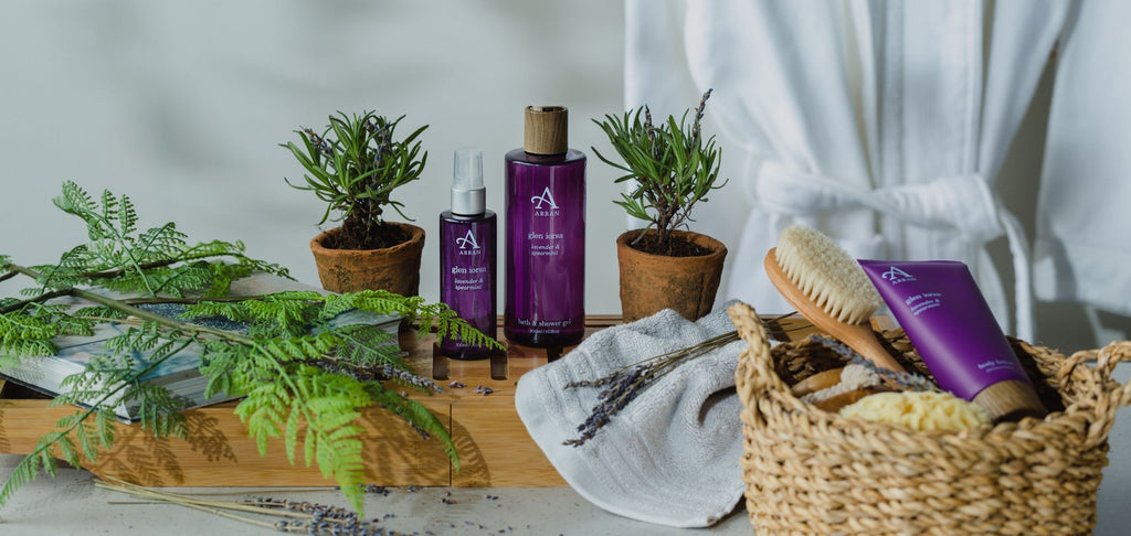 Image of lavender shower gel and body mist on wooden bath blank with white dressing robe in background.