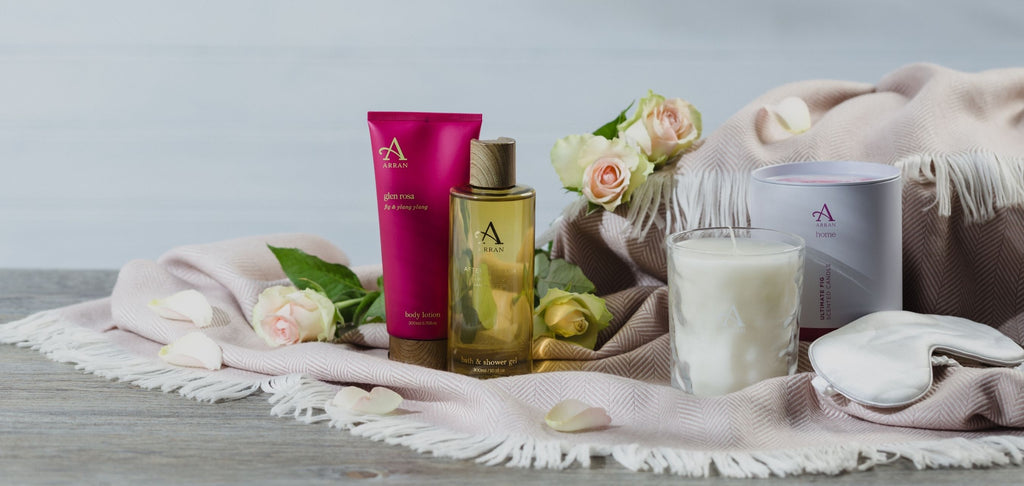 Image of assorted shower gels, body lotions and candles on wooden table with roses and pink blanket.