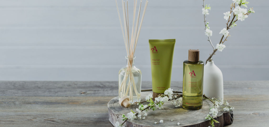 Image of green shower gel and body lotion and shower gel, placed on wooden table.
