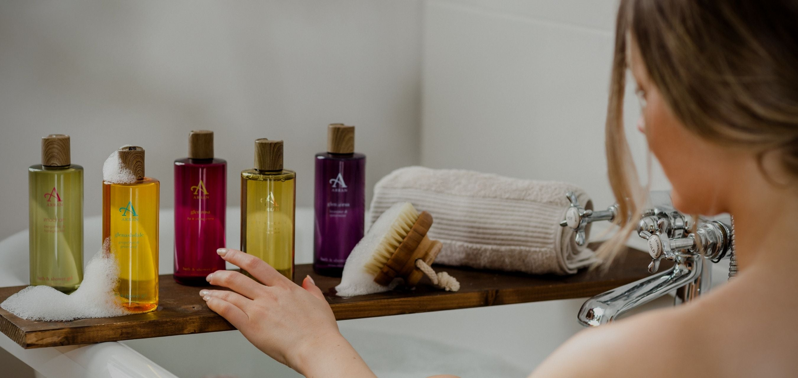 Woman in bath holding bath and shower gel bottle