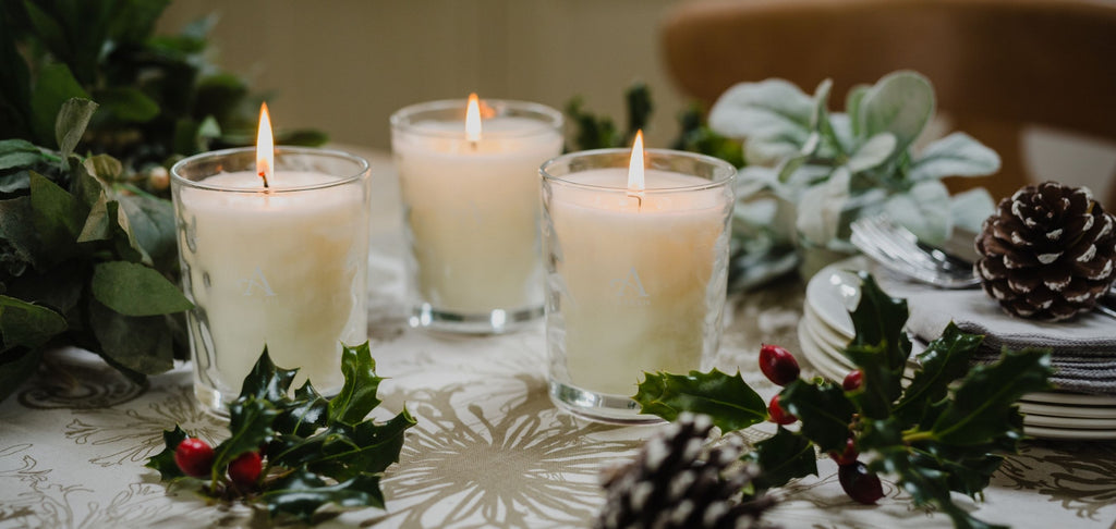 Three lit candles on dining room table, surrounded with foliage centrepiece.