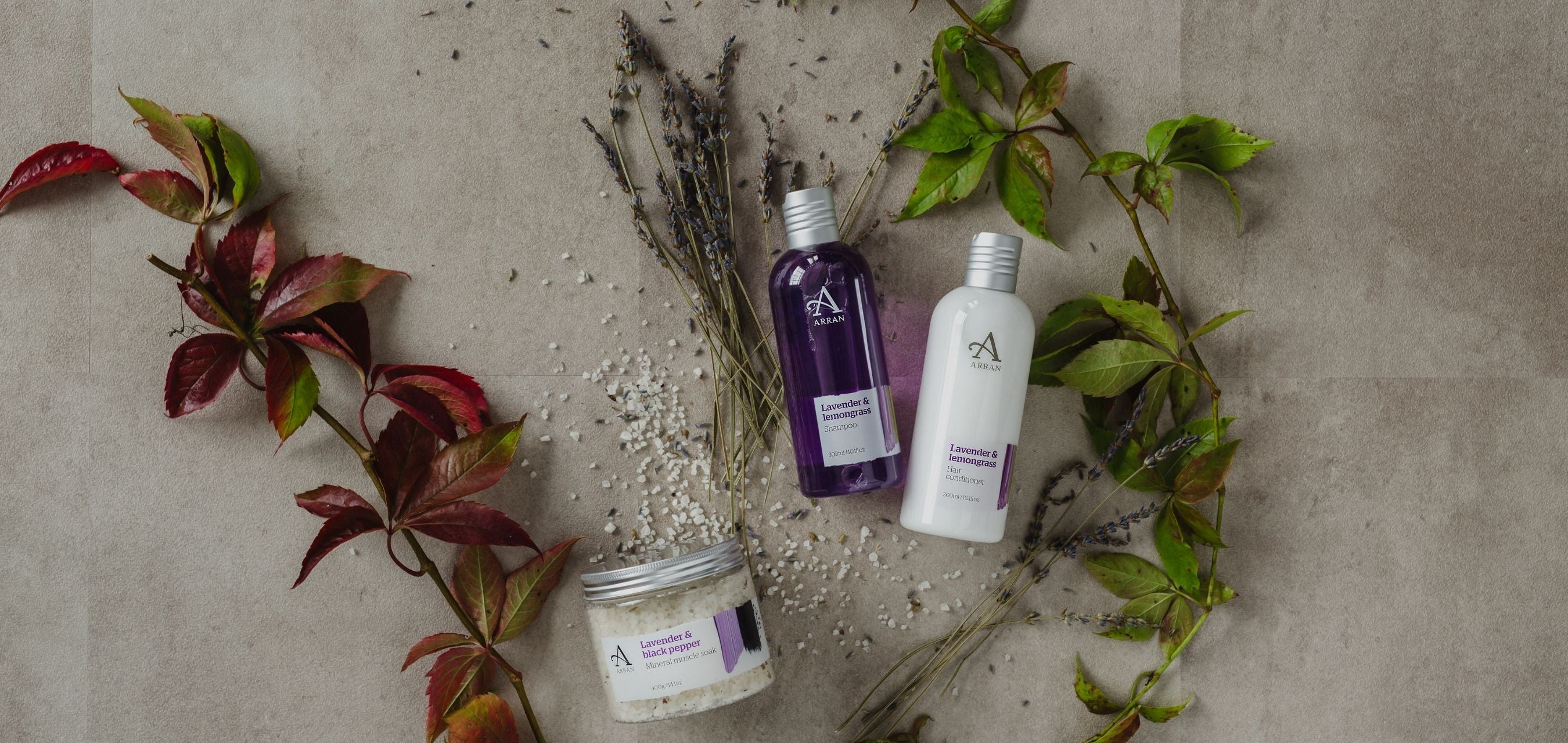 Lavender Shampoo, Conditioner and Bath Salts on grey concrete surrounded by green foliage.